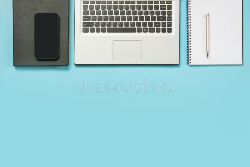 Arbeitsplatz mit offenem Laptop und Zusatz auf Büroblautabelle Draufsicht- und Kopienraum stockfotos