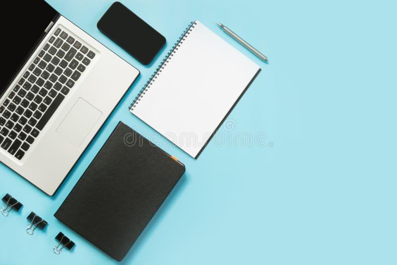 Arbeitsplatz mit offenem Laptop-, weißem und Schwarzemzusatz auf blauer Tabelle Draufsicht- und Kopienraum stockbilder