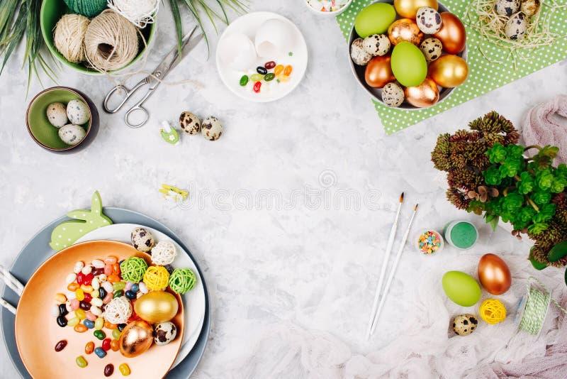 Arbeitsplatz mit Ostern-Dekoration Gemalte Eier in den Behältern, Süßigkeit, Blumen mit Kopienraum Gelbe und rote Farben stockbild