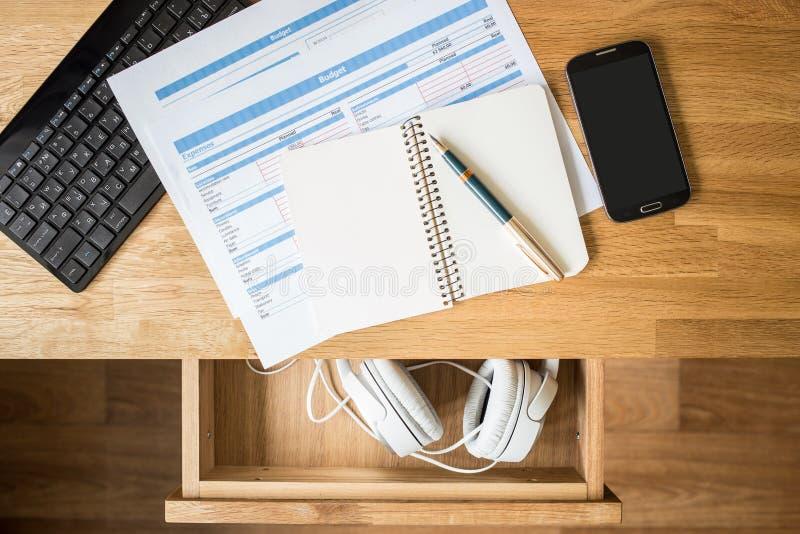 Arbeitsplatz mit Papieren und Kopfhörern im Fach stockfotos