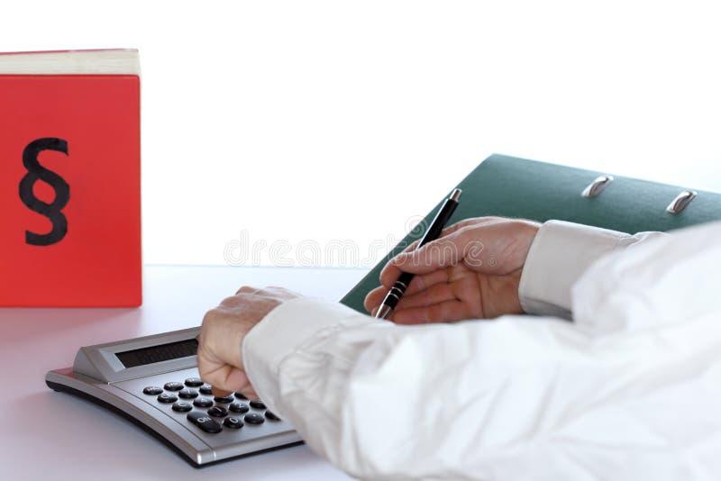 Arbeitsplatz mit Taschenrechner und Gesetzbuch lizenzfreie stockbilder