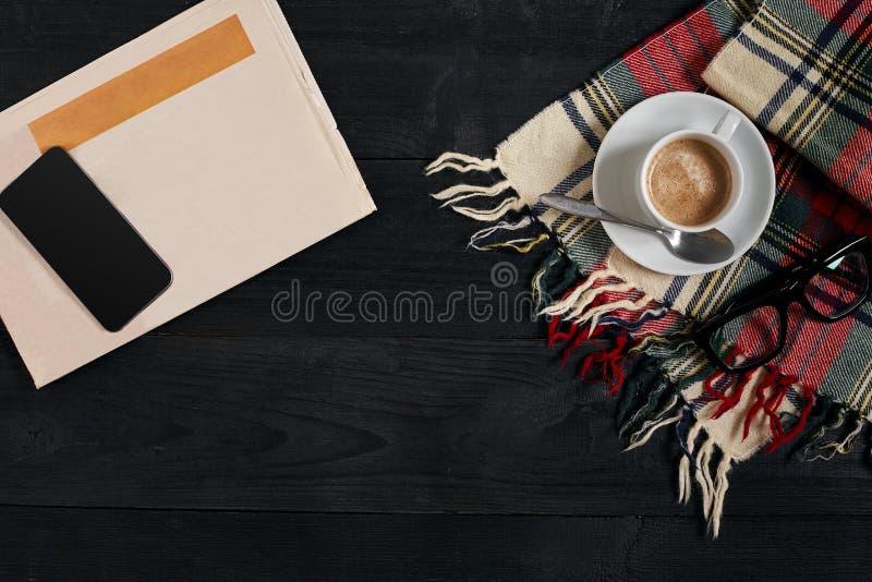 Arbeitsplatz mit Zeitung, Kaffeetasse, Schal, Gläser Stilvoller Schreibtisch Herbst- oder Winterkonzept Flache Lage, Draufsicht stockbild