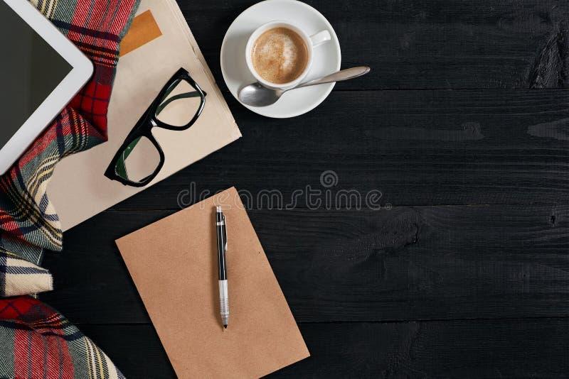 Arbeitsplatz mit Zeitung, Kaffeetasse, Schal, Gläser Stilvoller Schreibtisch Herbst- oder Winterkonzept Flache Lage, Draufsicht lizenzfreies stockfoto