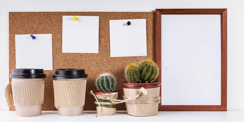 Arbeitsplatz-Modell Skandinavische Artfahne Drei weiße Aufkleber, leerer vertikaler Rahmen, zwei Tasse Kaffees, Kaktus zwei auf e stockbilder