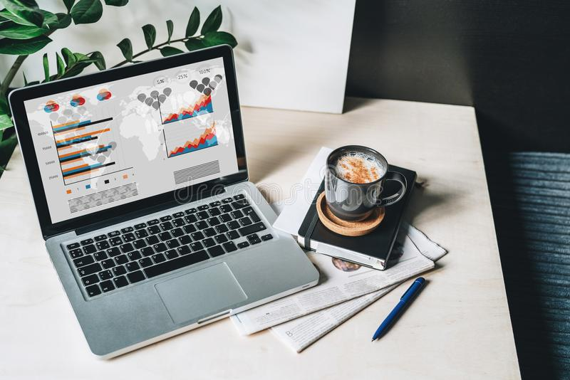 Arbeitsplatz ohne Leute, Nahaufnahme des Laptops mit Diagrammen, Diagramme, Diagramme auf Schirm auf weißer Tabelle, Schreibtisch lizenzfreie stockfotografie