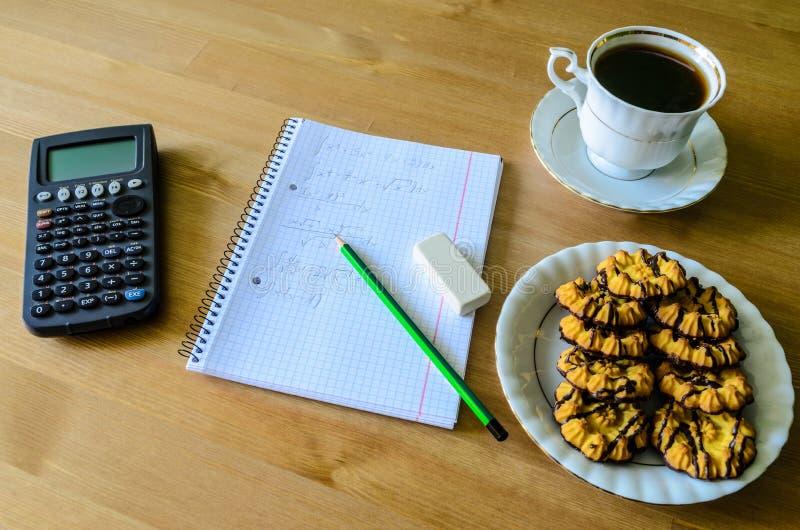 Arbeitsplatz, Studienplatz mit Taschenrechner, Arbeitsbuch, Tasse Kaffee stockfoto