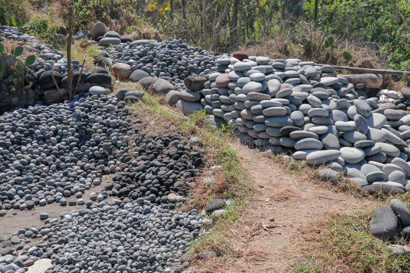 Arbeitsplatz von Balinesesteinsammlern Sortierte Flusssteine durch Größe Nat?rliches Baumaterial Harte Arbeit Steine geworfen vom stockbilder