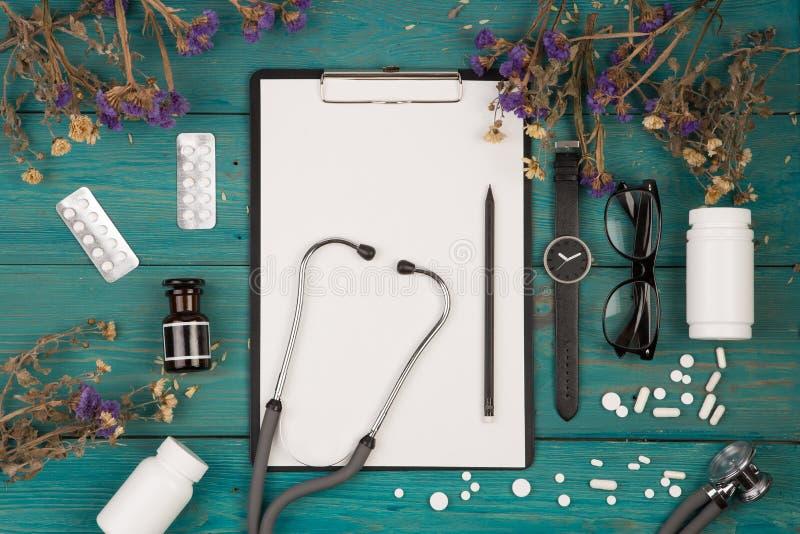 Arbeitsplatz von Doktor - Stethoskop, Medizinklemmbrett, Flasche, f stockbild