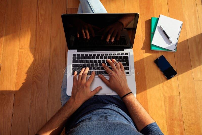 Arbeitsplatz zu Hause Student, der mit einem Laptop auf dem Boden arbeitet lizenzfreie stockfotografie