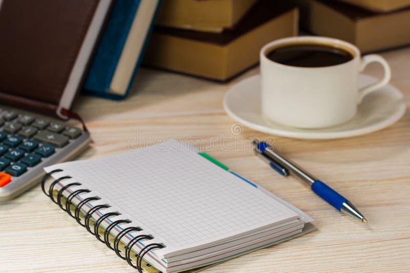Arbeitsplatzbuchhalter Taschenrechner mit einem Notizblock nahe bei dem heißen oben zuzujubeln Kaffee, lizenzfreie stockbilder