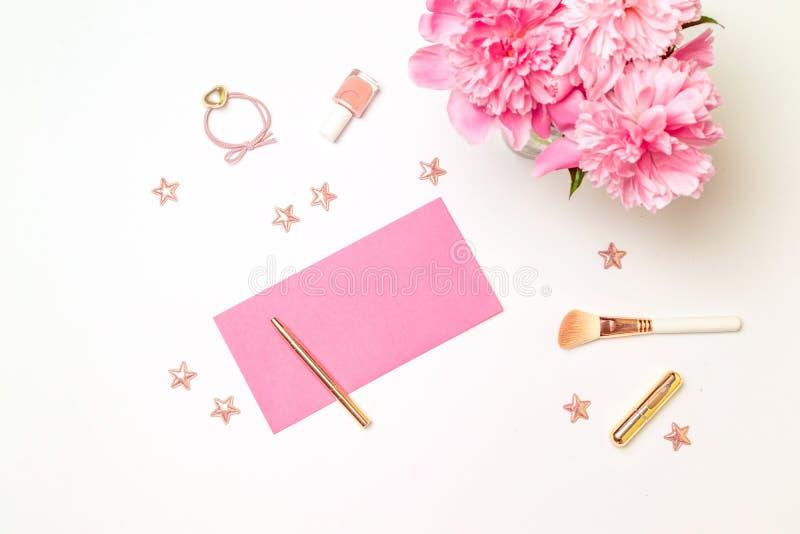 Arbeitsplatzhochzeitseinladungs-Kartenmodell der Draufsicht weibliches mit Pfingstrosenblumen auf rosa Hintergrund Flache Lage stockfotos