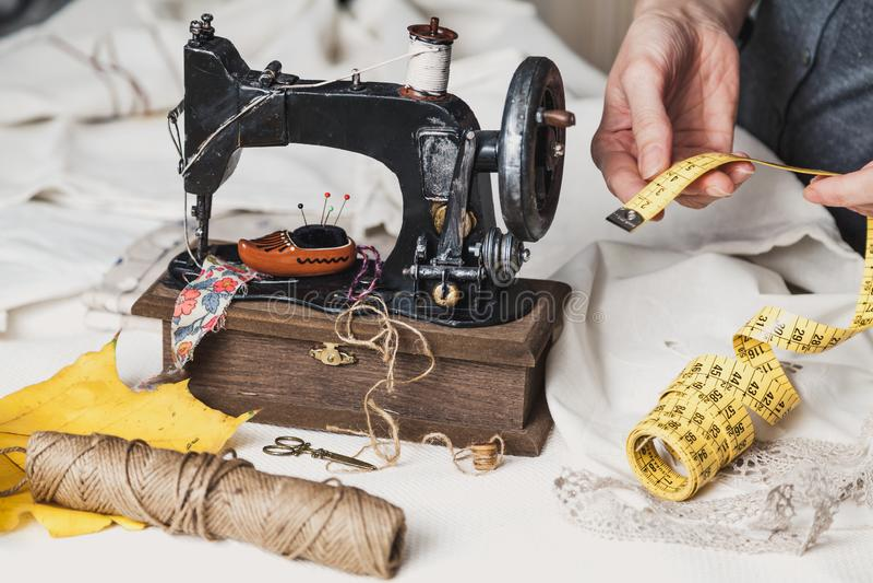 Arbeitsplatznäherin Nähmaschine der Weinlese und ein Strang von Threads Ein gelbes Ahornblatt liegt nahe bei ihm Die Hände der Fr lizenzfreies stockbild