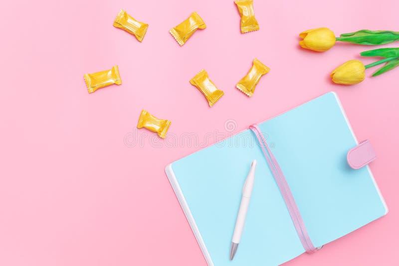 Arbeitsplatzschreibtisch redete Entwurfsb?roartikel, -s??igkeit und -blume auf minimaler Art des rosa Pastellhintergrundes an lizenzfreies stockbild