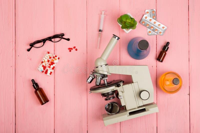 Arbeitsplatzwissenschaftler/Doktor - Mikroskop, Pillen, Spritze, Brillen, chemische Flaschen mit Flüssigkeit auf rosa Holztisch stockfoto