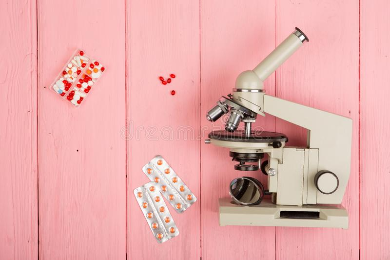 Arbeitsplatzwissenschaftlerdoktor - Mikroskop, Pillen auf rosa Holztisch lizenzfreies stockbild