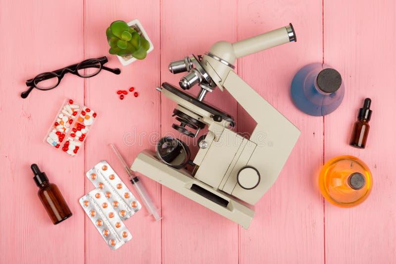 Arbeitsplatzwissenschaftlerdoktor - Mikroskop, Pillen, Spritze, Brillen, chemische Flaschen mit Flüssigkeit auf rosa Holztisch lizenzfreie stockfotografie
