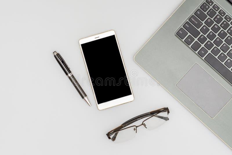 Arbeitsplatzzusammensetzung der Laptop-Computers, des Smartphonestiftes und der gefalteten Gläser auf Schreibtischtabellenhinterg stockfotografie
