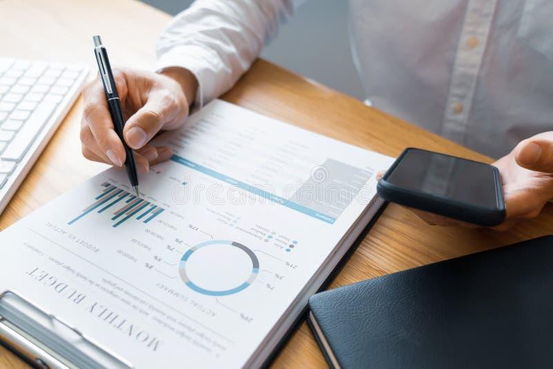 Arbeitsprozesskonzept, Geschäftsmann unter Verwendung des Handyschreibens in der Tagesordnung zu Hause beraten auf einem Schreibt stockfotografie