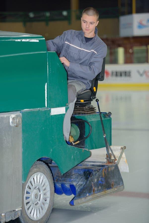 Arbeitsreinigung des jungen Mannes auf Eisbahn stockfoto