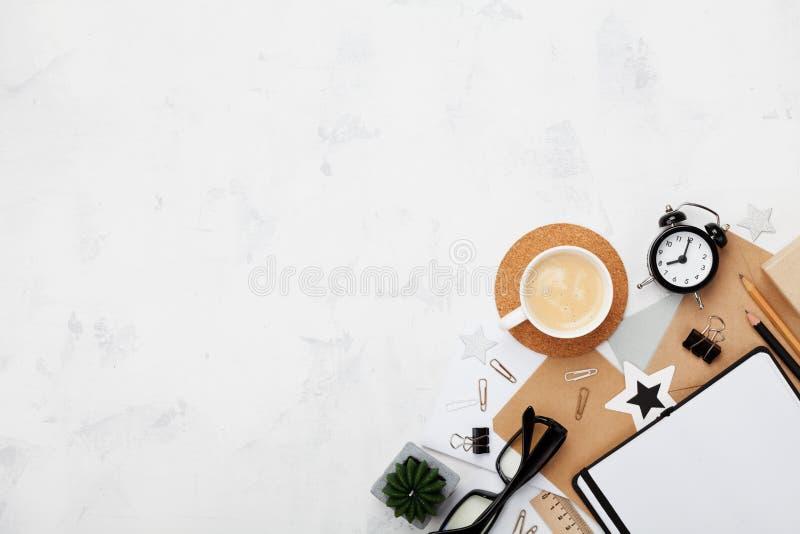 Arbeitsschreibtisch des stilvollen Blogger mit Kaffee, Bürozubehör, Wecker und sauberem Notizbuch auf weißer Tischplatteansicht F stockbild