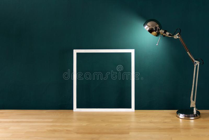 Arbeitsschreibtisch im dunkelgrünen Raum verziert mit dem weißen Fotorahmen lizenzfreie stockbilder