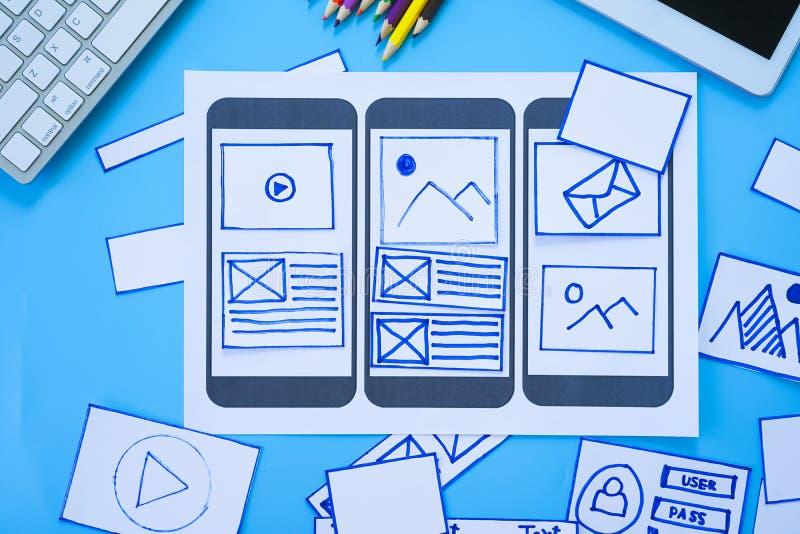 Arbeitsschreibtisch mit den Händen, die wireframe Schirme der beweglichen entgegenkommenden Website sortieren Sich entwickelndes  lizenzfreies stockbild
