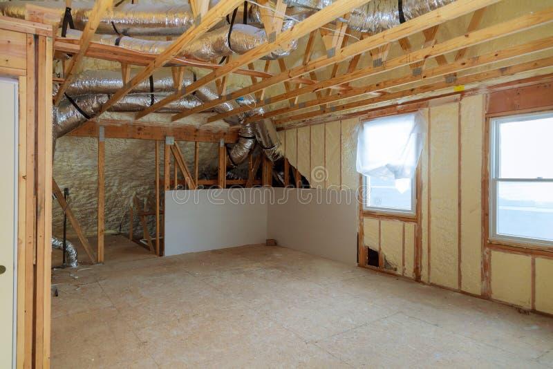 Arbeitsstandort der Installierung thermischer Schaum polyurea Isolierung unter die Dachwollplatten und die hölzernen Planken lizenzfreies stockbild