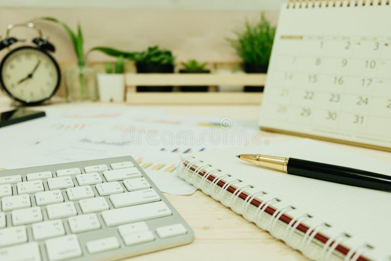 Arbeitstabelle mit Tastatur, Stift, Notizbuchpapier, Informationsdiagramm, Uhr stockfoto