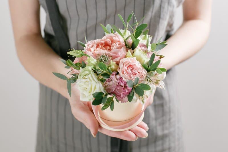 Arbeta blomsterhandlaren, bukett i en rund ask att lukta blommar hållande persikarosor i hatt mot den packade väggen arkivfoton