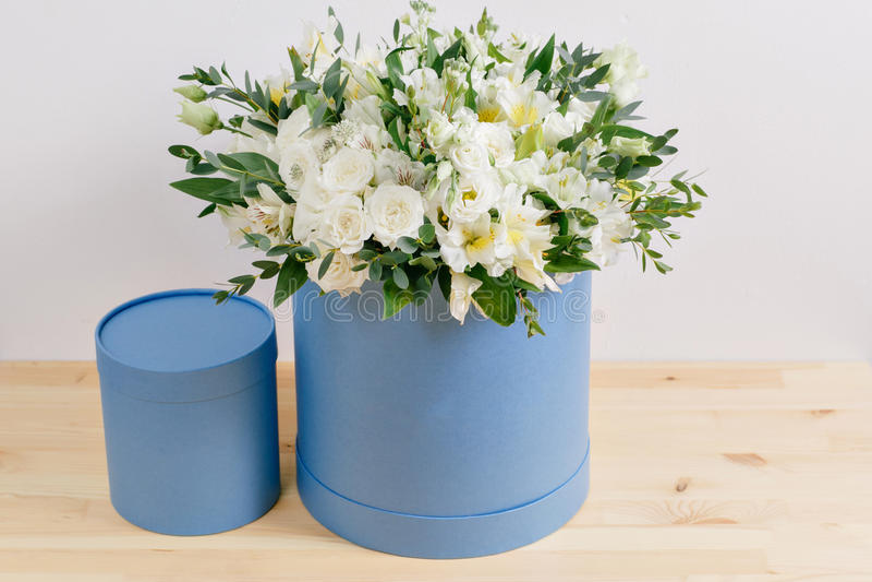 Arbeta blomsterhandlaren, bukett i en rund serenitetask att lukta blommar hållande vita rosor i hatt mot den packade väggen arkivbild