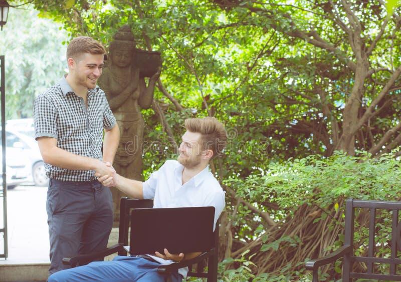 Arbeta för två amerikanskt affärspersoner av den glade framgången för för anteckningsbokdator och handskakning på utomhus- arkivbild