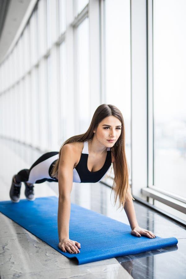 Arbeta hennes kärnamuskler Full längd av den unga härliga kvinnan i sportswearen som gör plankan, medan stå framme av arkivfoton
