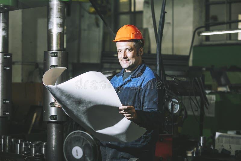Arbeta i produktion mot en bakgrund av maskiner från royaltyfria bilder