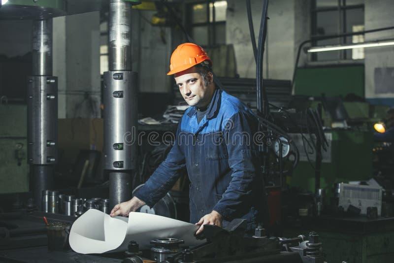 Arbeta i produktion mot en bakgrund av maskiner från arkivfoto