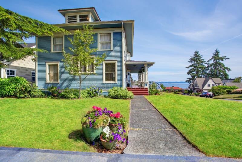 Arbeta i trädgården gammal amerikansk husyttersida för den klassiska stora hantverkaren i blåa signaler med den hållna brunnen royaltyfri bild