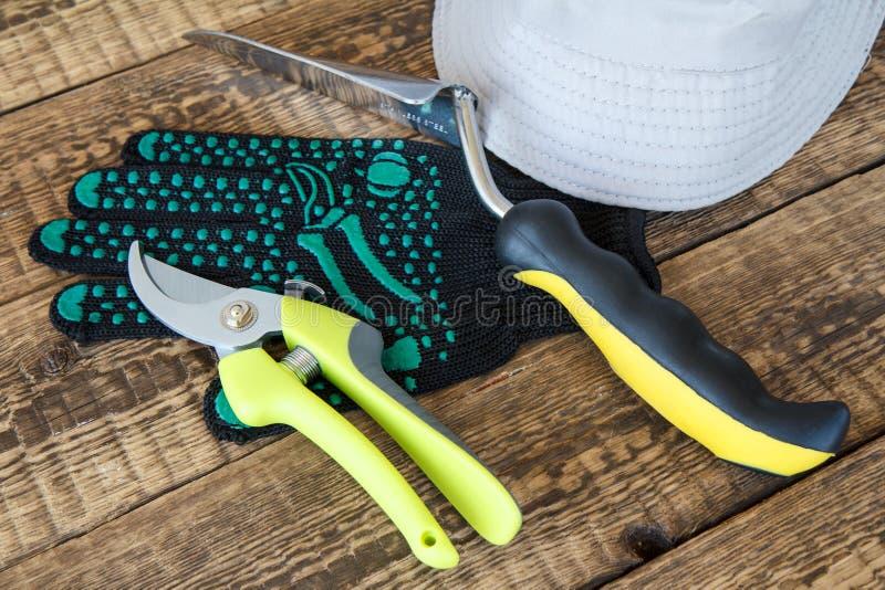 Arbeta i trädgården handsken, pruner, mursleven och hatten på träbräden royaltyfri bild