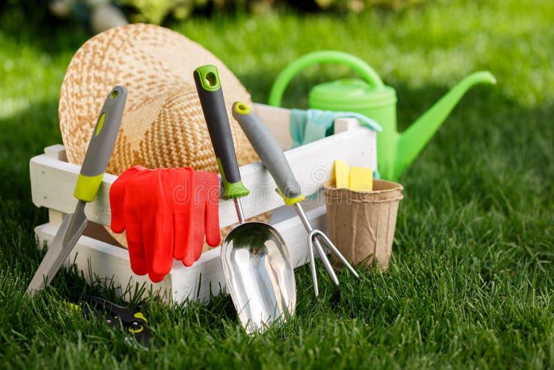 Arbeta i trädgården hjälpmedel, handskar, sugrörhatt och vit träask på grönt gräs, trädgårdunderhåll och hobbybegrepp arkivbilder