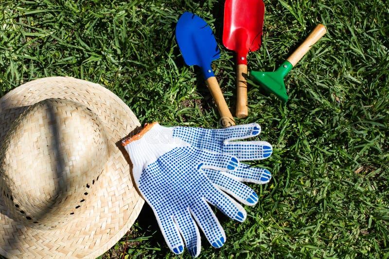 Arbeta i trädgården hjälpmedel och en hatt på gräset arkivfoto