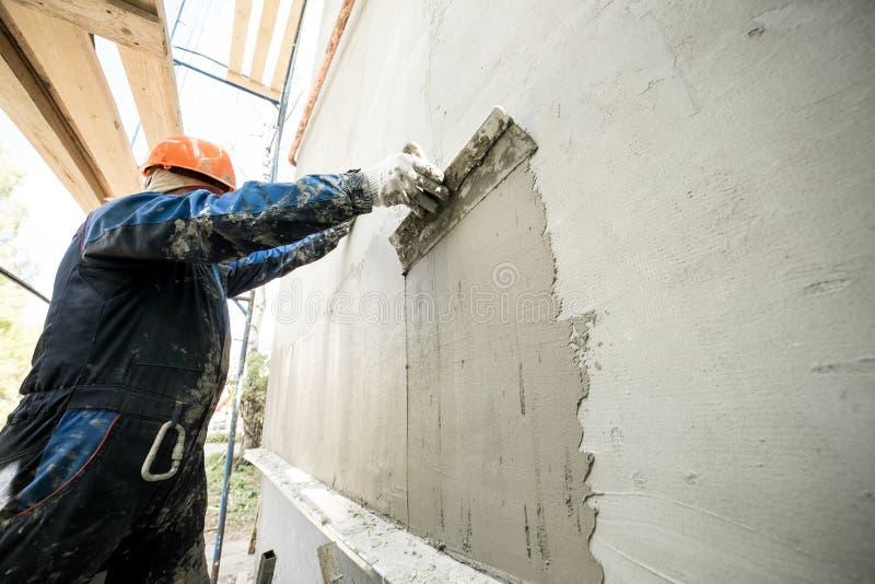 Arbeta med en spatel som förbereder väggarna för att belägga med tegel arkivfoton