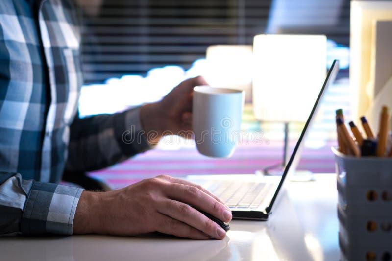 Arbeta sent på natten och dricka kaffe royaltyfria foton