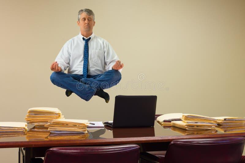 Arbeta släkt spänningslättnad med yoga som mannen som svävar över buntar av skrivbordsarbete och datoren arkivfoto