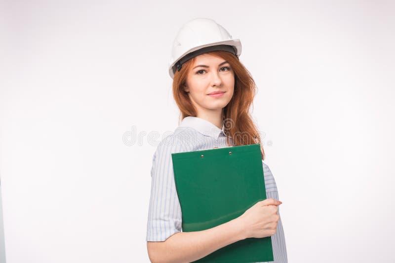 Arbeta som iscensätter, folkbegrepp - en kvinnlig tekniker i en hjälm med mappen över den vita bakgrunden royaltyfria bilder