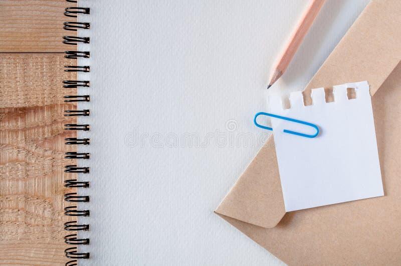 Arbeta utrymme, brevpapper, skissa boken med blåa gem papper, brevpapper, blyertspenna på trätabellen listan gör det, passande fö royaltyfri fotografi