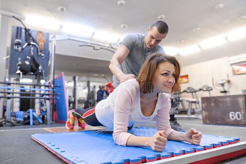 Arbetande övning för personlig konditioninstruktör med den mogna kvinnan i idrottshallen Vård- begrepp för konditionsportålder royaltyfria foton