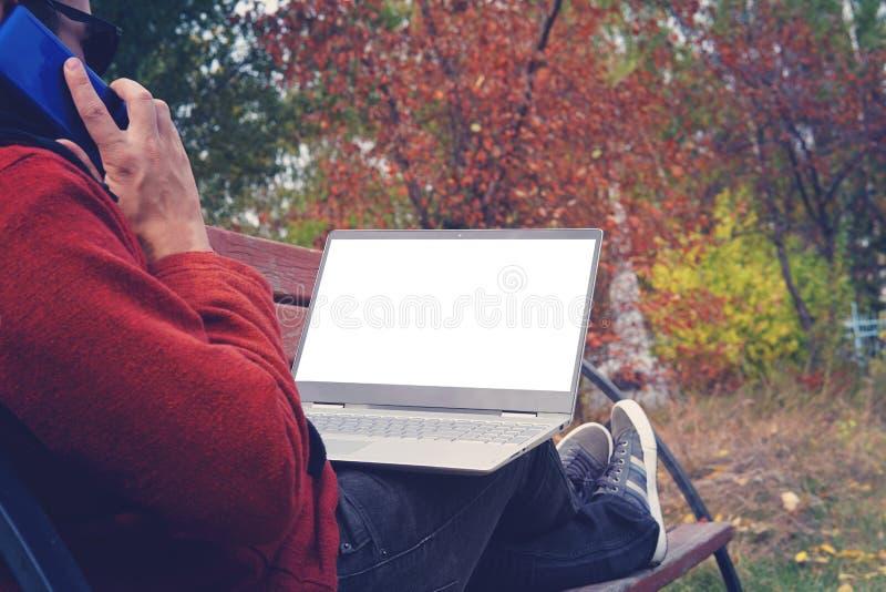 Arbetande det fria för man alltid förbindelse med hans smartphone och hans lojala bärbar dator ung grabb, arbetande det fria för  royaltyfri foto