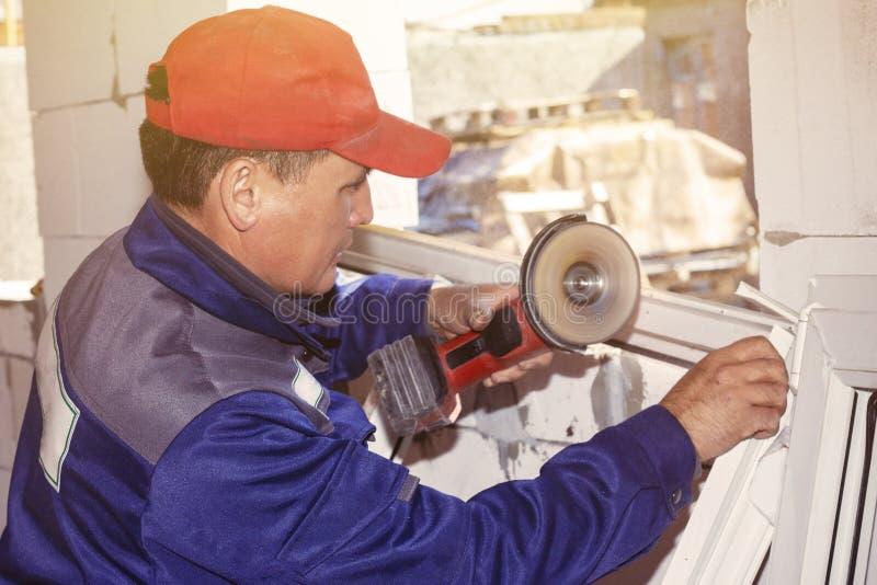 Arbetande för fönsterarbete för installation som plast- sågar bygger ett hus royaltyfria foton