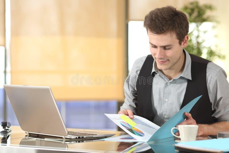 Arbetande hållande ögonen på statistik för affärsman arkivfoton