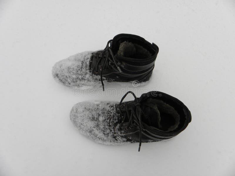 Arbetande kängor övervintrar våt, kall smutsig snö royaltyfri fotografi