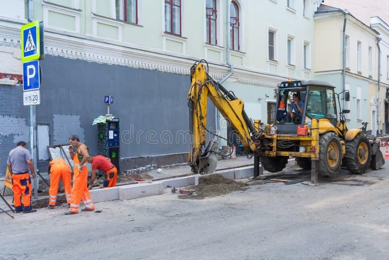 Arbetande lagändringskantsten med en grävskopa Vägarbeten på stadsgataledaren fotografering för bildbyråer