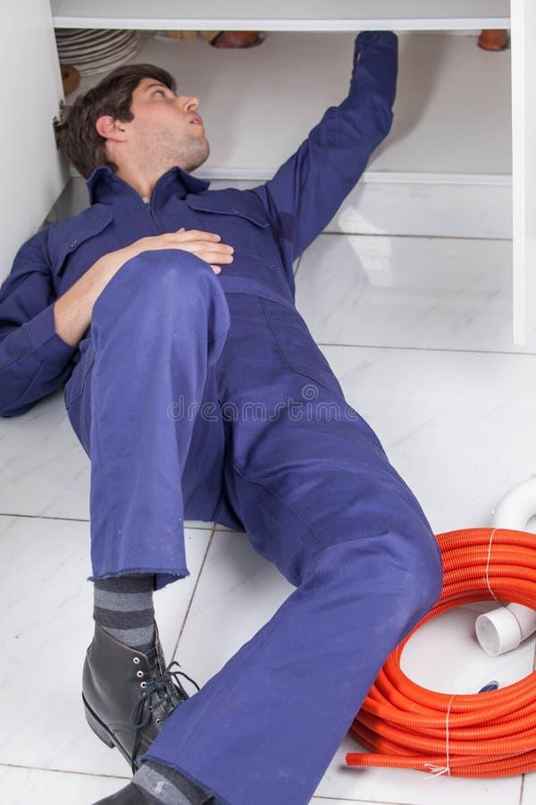 Arbetande ligga för rörmokare på golvet fotografering för bildbyråer
